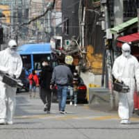 Quarantine workers spray disinfectant Monday at night spots in the Itaewon neighborhood of Seoul following a coronavirus disease outbreak in the area. | YONHAP / VIA REUTERS