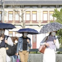 People shade themselves from unseasonably hot weather in the city of Kyoto on Monday. The government considered adding Kyoto Prefecture to the list of those where the state of emergency will be lifted, but then decided the move could be premature. | KYODO