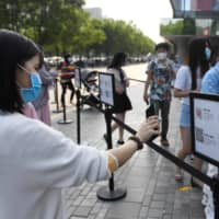 A woman uses a phone app to scan a code required to prove her health and travel status before being allowed to enter a shopping mall in Beijing on May 2.  | AFP-JIJI
