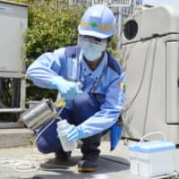 A Tokyo Metropolitan Government official collects a sample at a sewage treatment center in Tokyo's Minato Ward on Wednesday in an effort to detect the presence of the novel coronavirus. | KYODO
