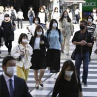 People wear masks while commuting to work in Tokyo's Ikebukuro district on Thursday. | KYODO