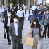 Commuters head to work in Tokyo's Ikebukuro district on Thursday as the government prepared to lift the state of emergency in many prefectures. | KYODO