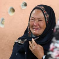 An Afghan woman cries Wednesday while looking for her relative at a Kabul hospital that came under attack the day before. | REUTERS