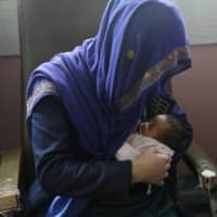 A mother breastfeeds her two-day-old baby Wednesday at the Ataturk Children's Hospital a day after they were rescued from a deadly attack on another maternity hospital in Kabul. | AP