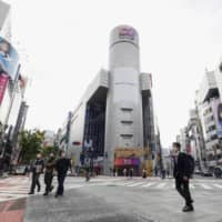 Far fewer people than usual walk on the scramble intersection in the Shibuya area of Tokyo on May 4. | KYODO