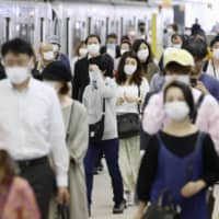 People wear face masks at Fukuoka Station on Thursday. | KYODO