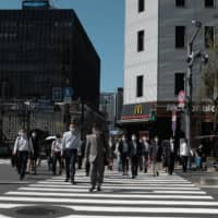 Pedestrians wearing protective masks cross a road in the Shimbashi district of Tokyo on Thursday. | BLOOMBERG