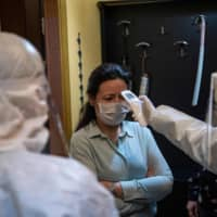 A health officer wearing protective clothing checks the temperature of a resident, believed to have been in contact with coronavirus patients, in Istanbul on May 7. In Istanbul, 1,200 teams of 'contact tracers' try to pinpoint every person that was in contact with a coronavirus patient in order to isolate them early on and break the chain of contamination. Experts estimate that the U.S. as a whole — which has seen more than 84,000 COVID-19 deaths, by far the most of any country — will need at least 100,000 contact tracers. | AFP-JIJI