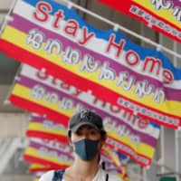 A woman wearing a protective mask walks below banners reading 'Stay Home' in Tokyo, where the state of emergency will remain in place despite being lifted in 39 other prefectures on Thursday. | REUTERS