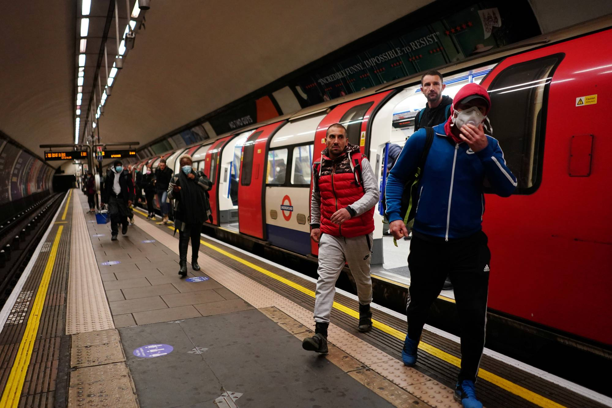 People step off a train at a subway station in London on Thursday. | REUTERS