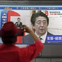 A monitor in the Dotonbori district in Osaka shows Prime Minister Shinzo Abe during a news conference on Thursday. | KYODO