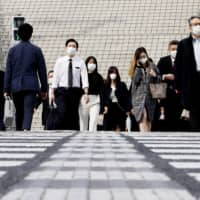 People walk by Nagoya Station in Aichi Prefecture while commuting on April 17.  | KYODO