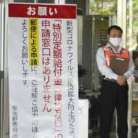 A sign asking residents to apply by mail to receive the ¥100,000 cash handout is seen in front of the Izumisano Municipal Government office in Osaka Prefecture on Tuesday. | KYODO
