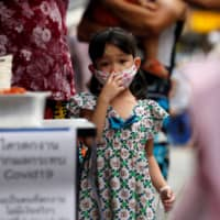 A daughter of a migrant worker family from Myanmar who lost their jobs lines up for free food from volunteers following the COVID-19 outbreak in Bangkok in April. | REUTERS