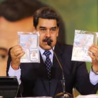 Venezuelan President Nicolas Maduro shows the passports of two U.S. citizens arrested by security forces during a meeting with international media May 6. | VENEZUELAN PRESIDENCY / VIA AFP-JIJI