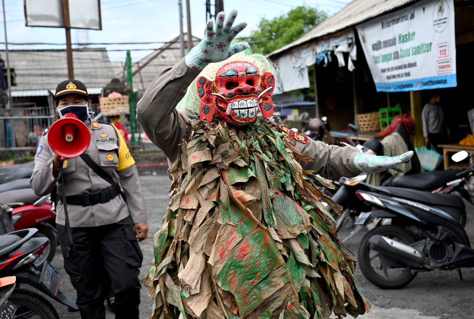 A Bali police officer wears a scary mask called 'Leak' while trying to educate people on COVID-19 at a traditional market in Kerobokan on Thursday. The island's success in curbing the virus has come with the help of about 1,500 traditional village committees with considerable sway over the majority Hindu residents, according to Gov. Wayan Koster. | AFP-JIJI