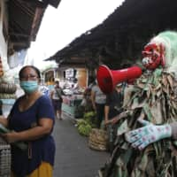 A Bali police officer wearing a traditional mask performs Thursday as the new coronavirus during a campaign at a market to get people to wear masks. | AP