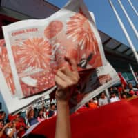 A China supporter holds up copies of the China Daily at Harbour City, Hong Kong, during China's National Day on Oct. 1 last year.  | REUTERS