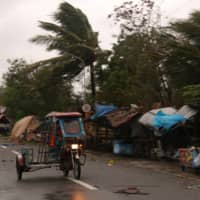 A man drives his tricycle along a road as strong winds caused by Typhoon Vongfong hit Catbalogan city, Western Samar province, Philippines, on Thursday.  | AP