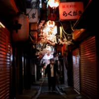 A man walks along a Tokyo street lined with restaurants and bars that are closed due to the coronavirus outbreak. Japan's nighttime entertainment business, premised on a male-dominated society and where men are mainly entertained by women, may gradually diminish in the post-pandemic era. | REUTERS