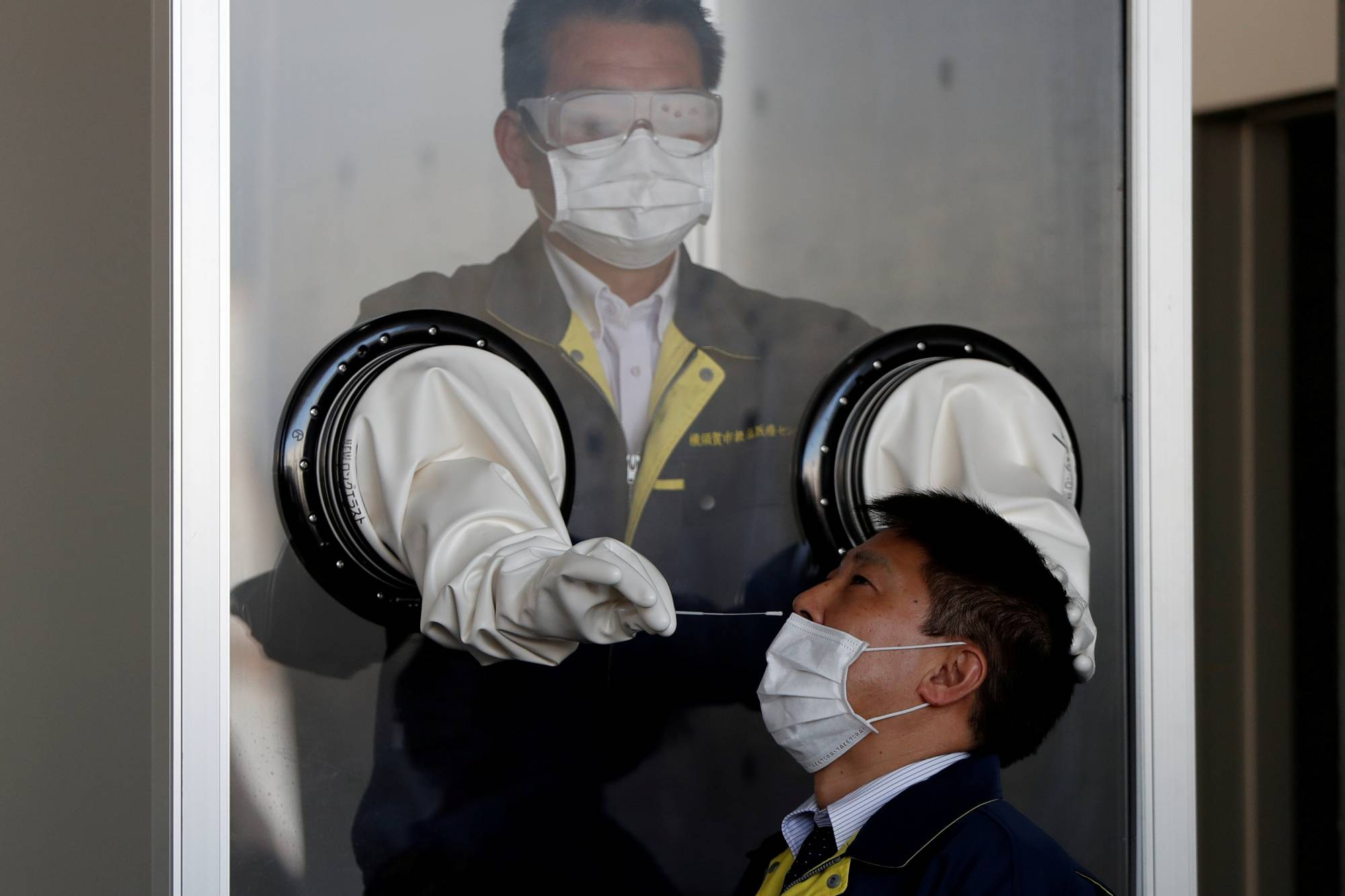 A medical worker conducts a simulation at a walk-in style polymerase chain reaction (PCR) test for the novel coronavirus at a makeshift facility in Yokosuka, Kanagawa Prefecture, on April 23. | REUTERS