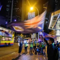 Hong Kong pro-democracy protesters wave the city's old colonial flag during a vigil outside the Pacific Place shopping mall in the Admiralty area on Friday. | AFP-JIJI