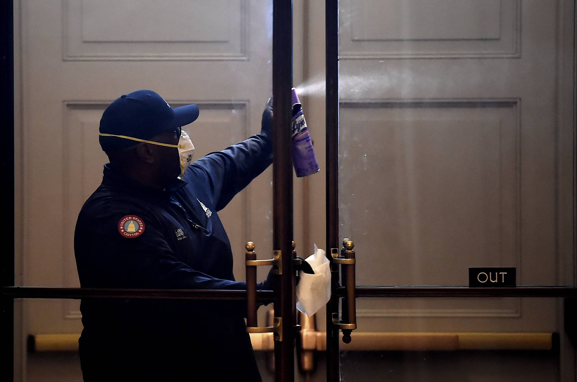 A worker, wearing protective gloves and a mask, disinfects a door inside of the U.S. Capitol in Washington on Friday amid the coronavirus pandemic. | AFP-JIJI