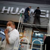 Workers wearing face masks fix the logo of Chinese electronics manufacturer Huawei at a mobile phone store in Beijing on April 24. | REUTERS