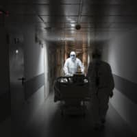 Medical workers move a coronavirus patient at an intensive care unit of the Filatov City Clinical Hospital in Moscow on Friday.   AP