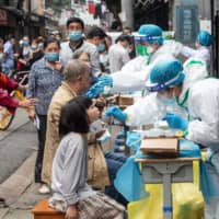 Medical workers take swab samples from residents to be tested for the COVID-19 coronavirus on a street in Wuhan, China, on Friday.   AFP-JIJI