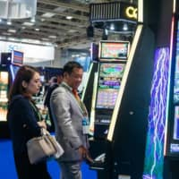 Customers play a slot machine at the Venetian Macao resort and casino, run by a unit of Las Vegas Sands Corp. in Macao. The company's withdrawal from its quest to win permission to build an integrated casino resort is a major setback in Japan's efforts to introduce casinos. | BLOOMBERG
