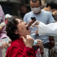 A medical worker takes a swab sample from a resident to be tested for COVID-19 on a street in Wuhan, China, on Friday. | AFP-JIJI