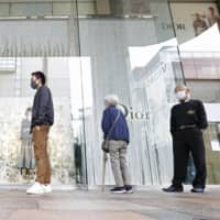 People keep their distance in a line at a bookstore that reopened Saturday in the Tenjin area of Fukuoka. The government last week removed Fukuoka Prefecture from the nationwide state of emergency over the novel coronavirus. | KYODO