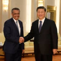 World Health Organization Director-General Tedros Adhanom Ghebreyesus shakes hands with Chinese President Xi jinping before a meeting at the Great Hall of the People in Beijing on Jan. 28. | POOL / VIA REUTERS