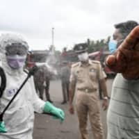 A police officer sprays disinfectant on a man planning to travel by bus to his hometown after the government ended a COVID-19 lockdown, in Kalutara, Sri Lanka, on Saturday.  | AFP-JIJI