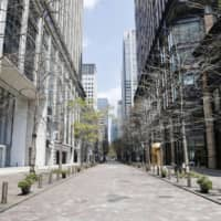 Fewer people than usual walk in Tokyo's Marunouchi business district on April 8 a day after Prime Minister Shinzo Abe declared a state of emergency in the capital and six other prefectures in response to a recent surge in coronavirus infections. | KYODO