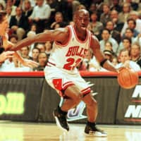 Chicago star Michael Jordan sticks out his tongue as he goes past Utah's Jeff Hornacek during Game 2 of the NBA Finals on June 4, 1997, in Chicago. | AFP-JIJI