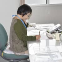 A woman takes a phone call from a person suffering a mental health issue at her office in Saitama on May 12.  | KYODO