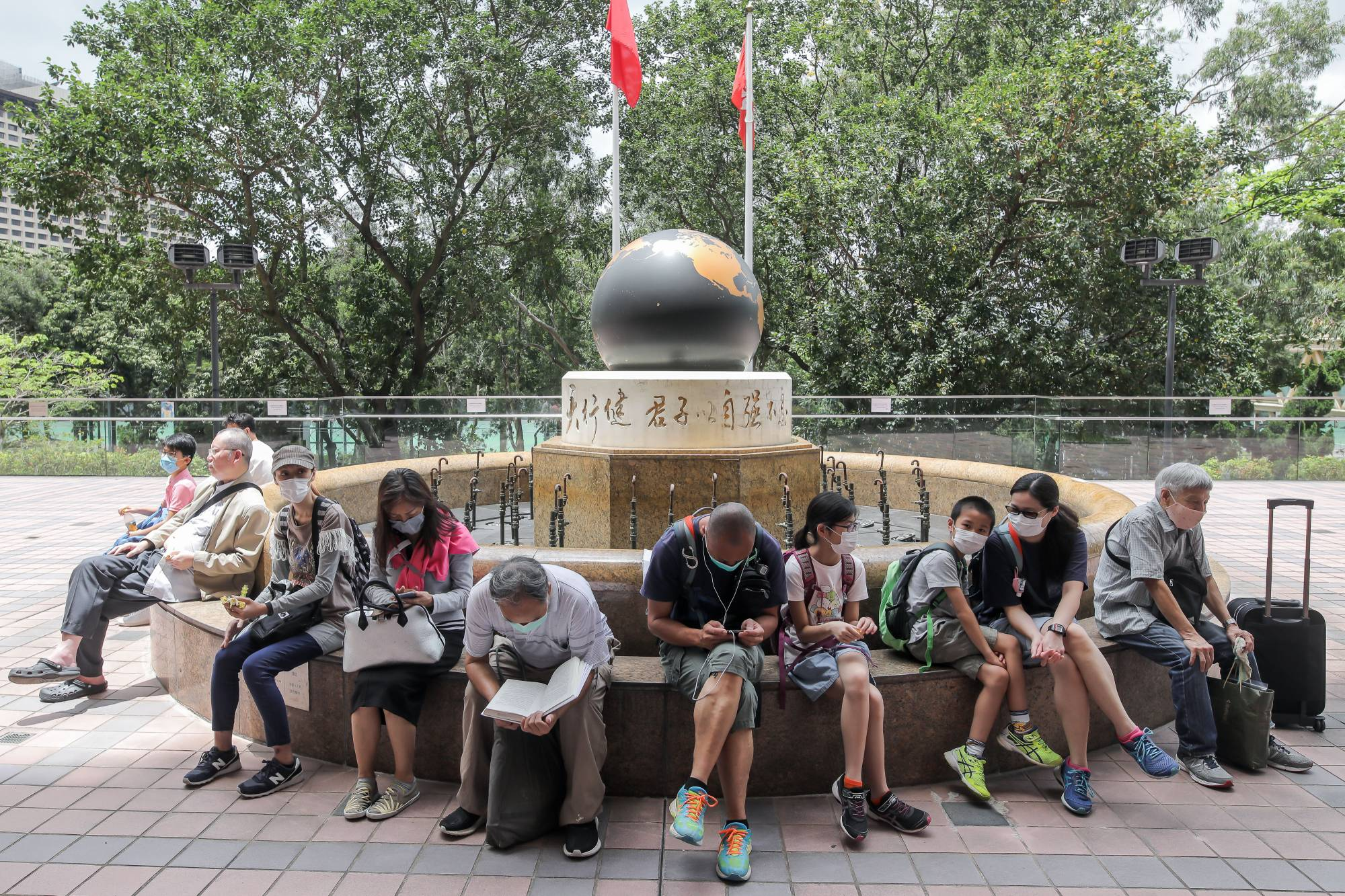 People sit outside the Central Library in the Causeway Bay district of Hong Kong, China, on May 6 after the city's leader, Carrie Lam, moved to loosen curbs on social gatherings and reopen shuttered schools. | BLOOMBERG