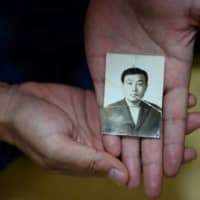 This photo taken on May 14, 2020, shows Jung Ki-young holding the only remaining photo of his father, Choi Jung-hwa, who disappeared during the Gwangju Uprising.    | AFP-JIJI