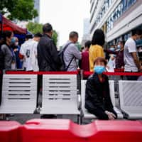 People queue up to be tested for coronavirus in Wuhan, the Chinese city hit hardest by the COVID-19 outbreak, on Saturday.  | REUTERS