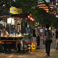 People walk past a street stall in the city of Fukuoka on Saturday after a coronavirus state of emergency was lifted in 39 of Japan's 47 prefectures, including Fukuoka on Thursday. | KYODO