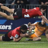 The Crusaders' Codie Taylor (below left) dives across the line to score a try as teammate George Bridge flies above him during the Super Rugby final between the Crusaders and the Jaguares on July 6, 2019, in Christchurch, New Zealand. | AP