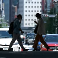 People walk on a street in Tokyo's Ginza shopping district on Sunday. | AFP-JIJI