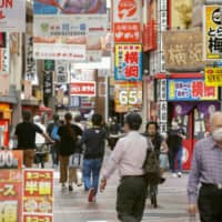 People stroll down a shopping street in Osaka City's Umeda district on Sunday. | KYODO