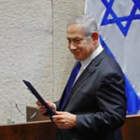 Israeli Prime Minister Benjamin Netanyahu leaves the podium during a swearing-in ceremony of the new government in Jerusalem on Sunday. | KNESSET SPOKESPERSON OFFICE / HO / VIA AFP-JIJI