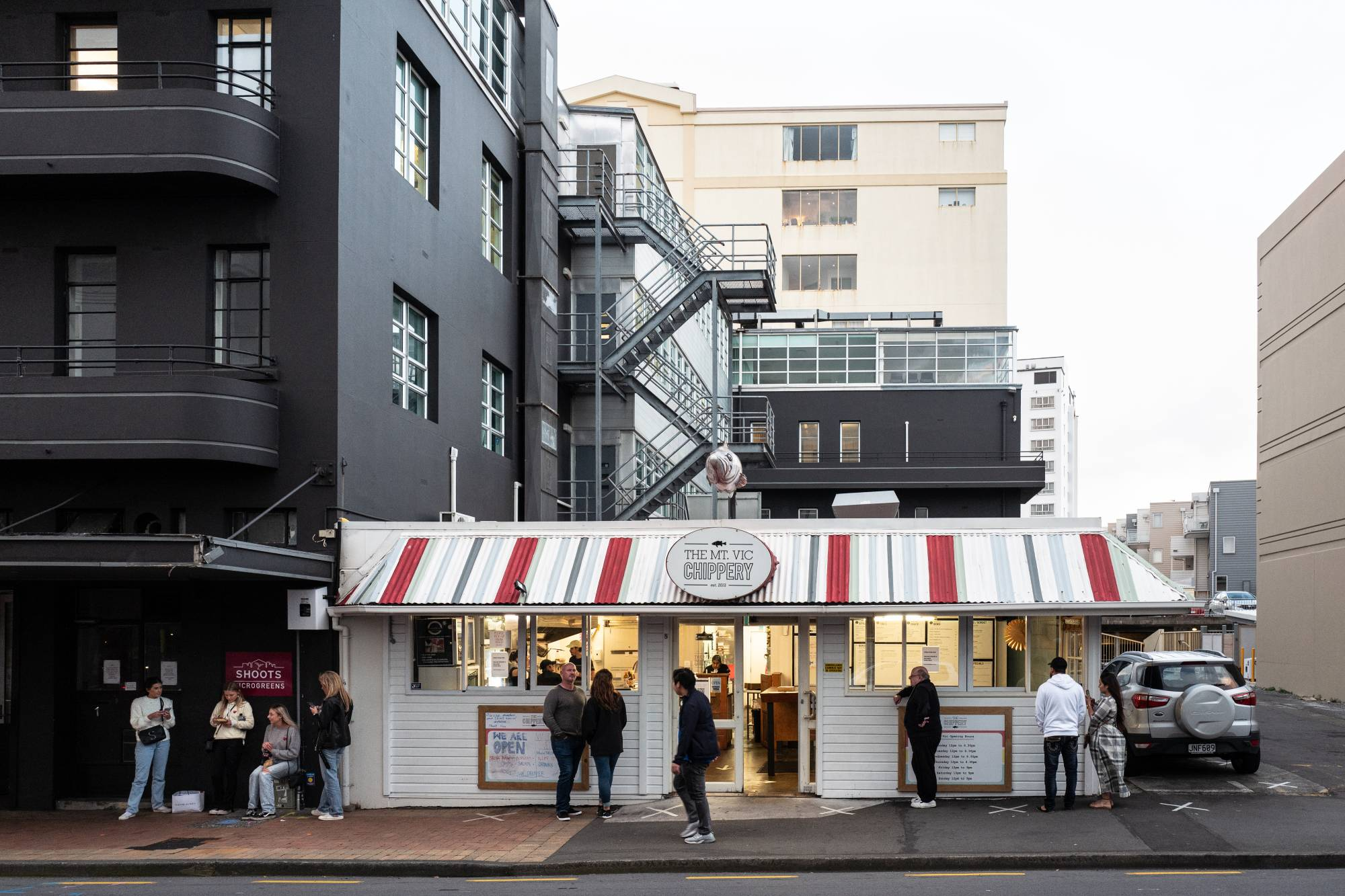 Customers maintain social distancing while they wait outside a fast food restaurant during a staged exit from New Zealand's coronavirus lockdown in Wellington on Thursday. | BLOOMBERG
