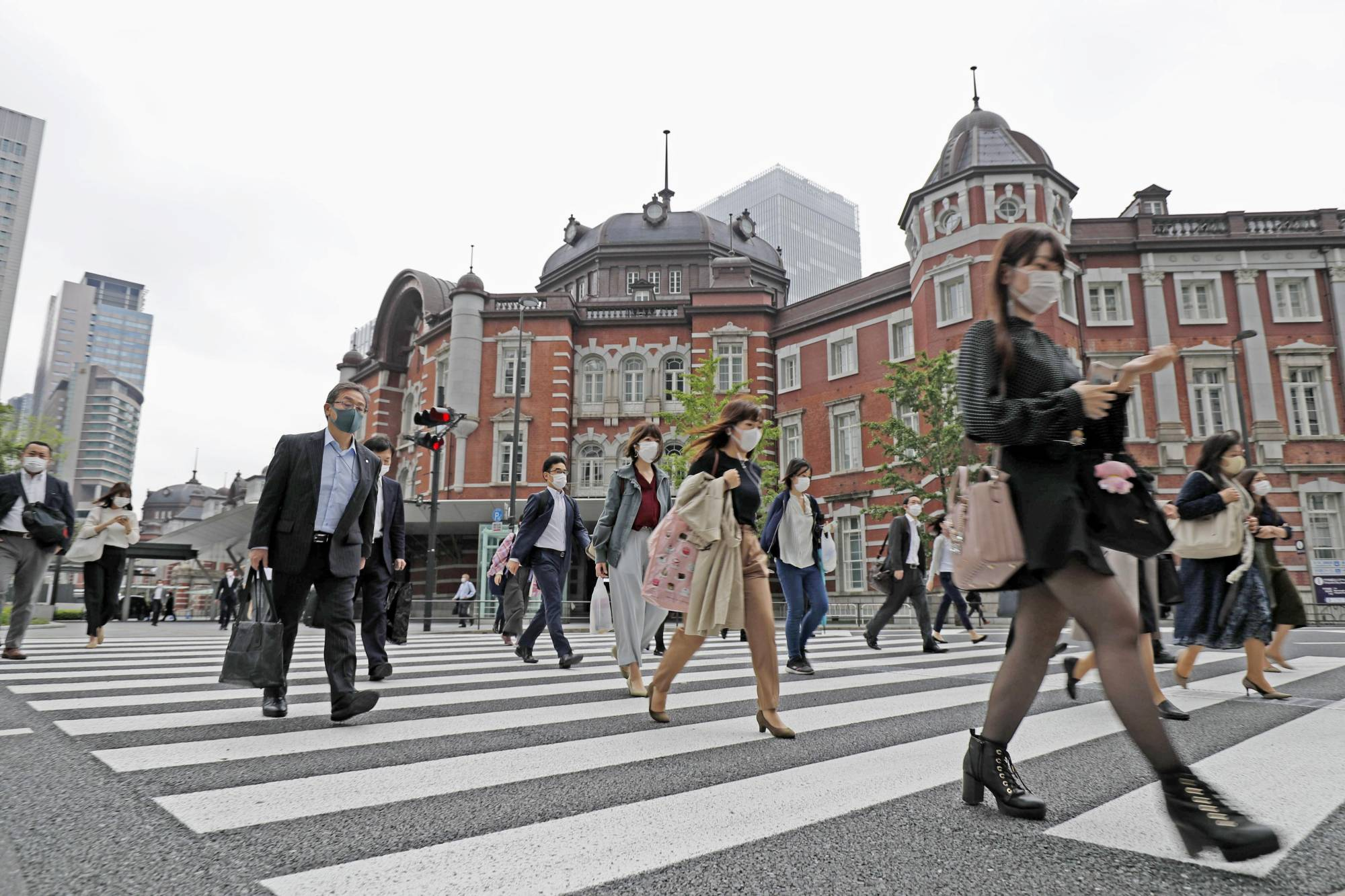 People going to work are seen outside the Tokyo Station on Monday. Japan's economy slipped into a recession in the three months through March. | KYODO
