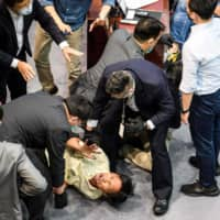 Pro-democracy lawmaker Eddie Chu (bottom center) is surrounded by security forces as he and other pro-democracy lawmakers scuffle with pro-Beijing lawmakers at the Legislative Council in Hong Kong on Monday. | AFP-JIJI