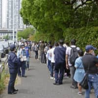 Foreign residents queue in front of Tokyo Regional Immigration Bureau on May 12. Its entry restrictions have sparked a strong reaction from the international community in Japan. | KYODO